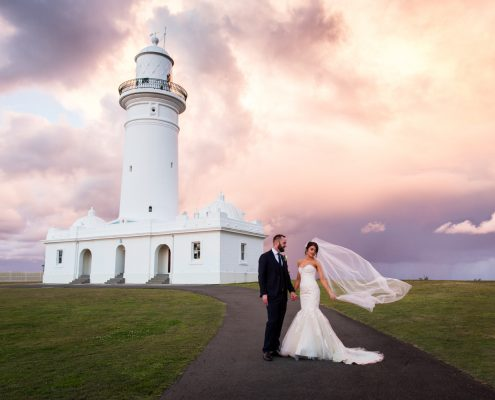 brides veil flying in the wind after wedding ceremony in front of lighthouse