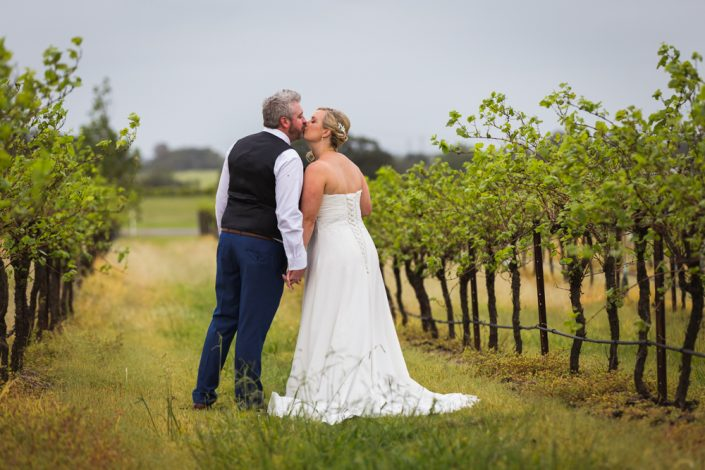 bride and groom kissing in the winery at the hunter valley