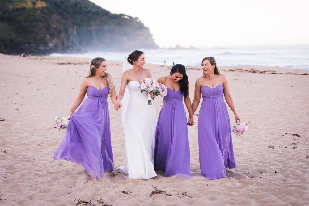 bridesmaids walking along the beach at wedding