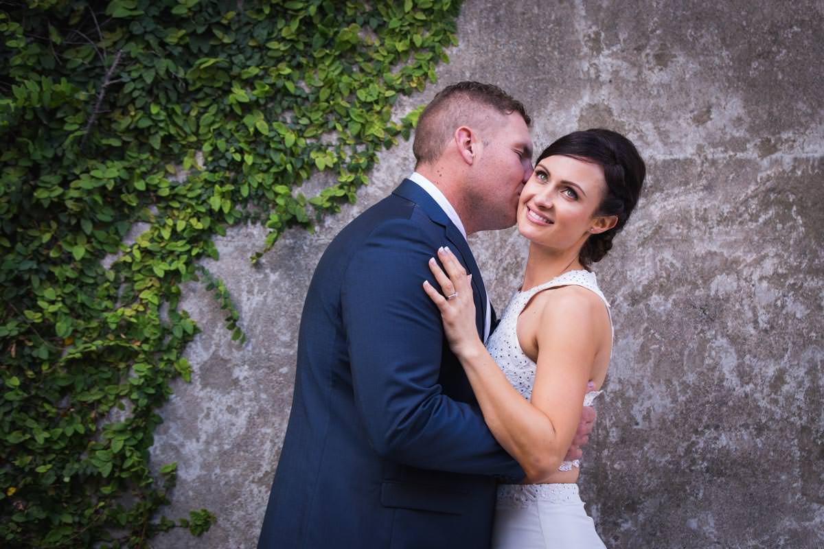 groom kissing bride on cheek at wedding