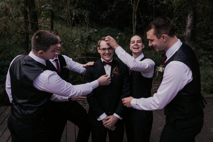groomsmen roughing up groom before wedding